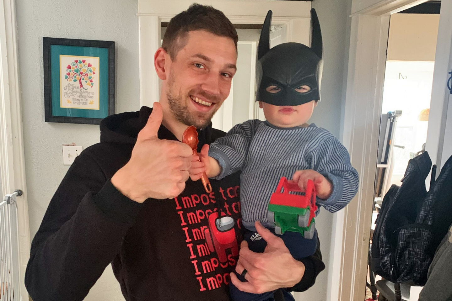 Dionysian Josts gives a thumbs up while holding his son, Gabriel, who is wearing a Batman mask.