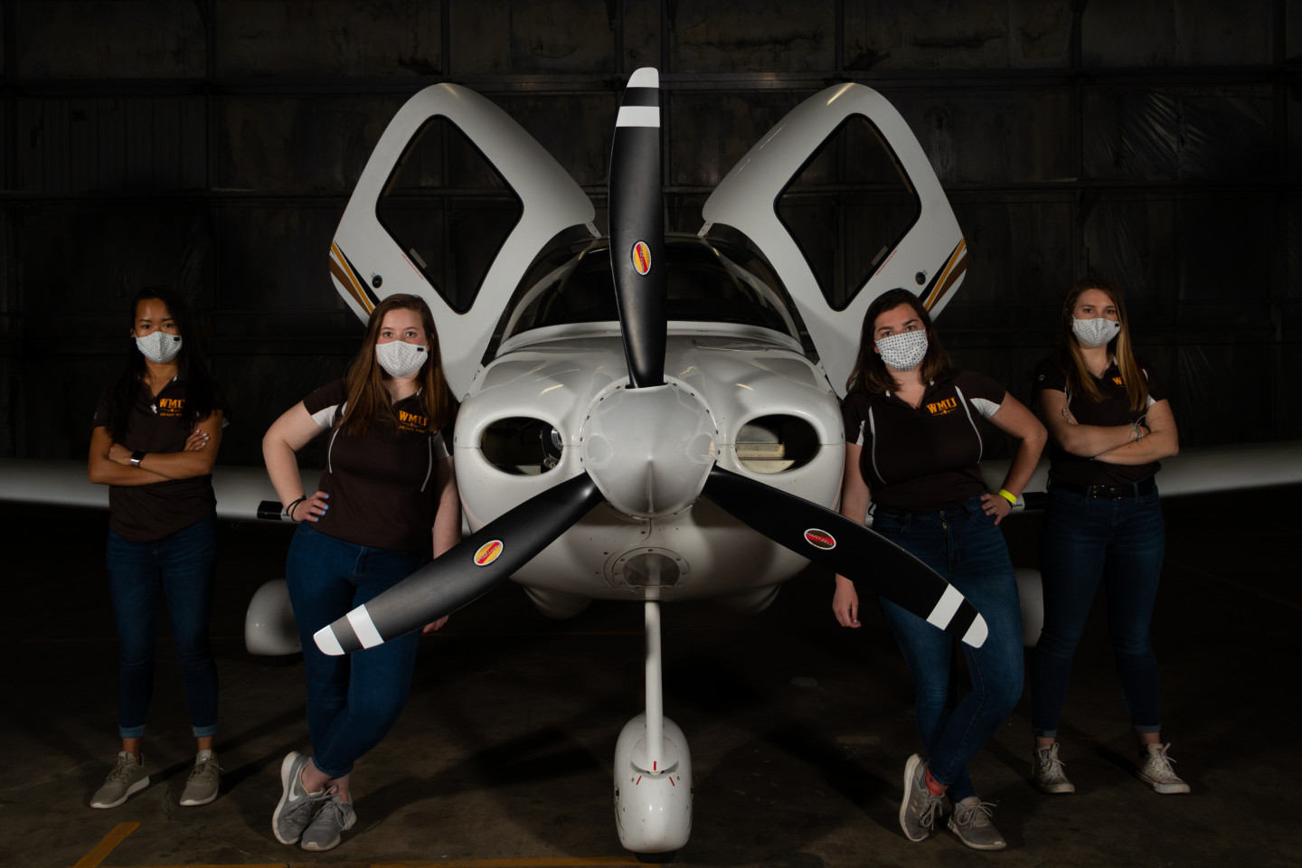 Four aviation students standing in front of a plane.