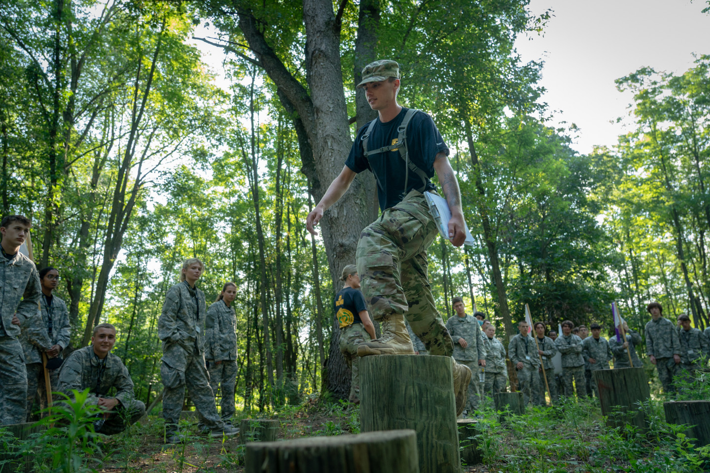 An ROTC cadet walks across stumps on an obstacle course.