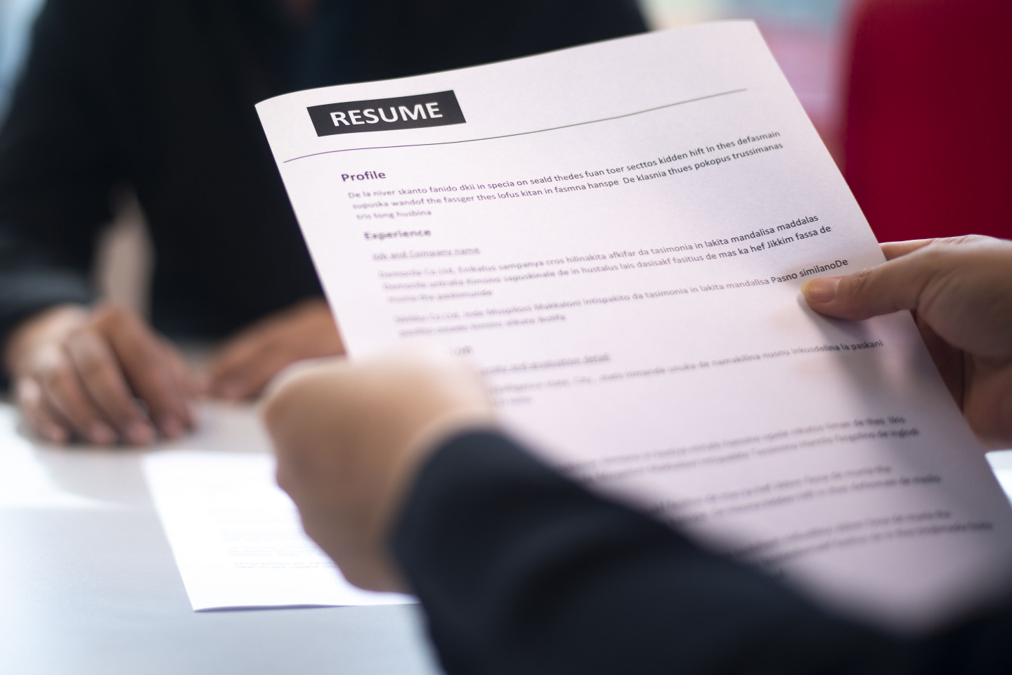 Photo of a resume held in a person's hands.