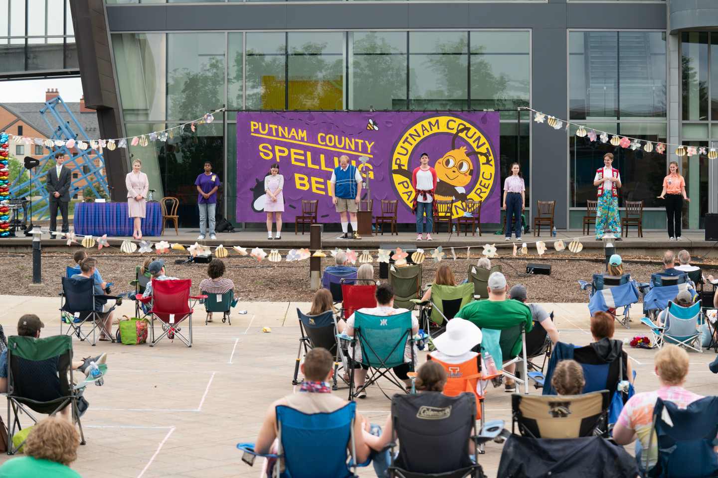 """An audience watches a production of """"The 25th Annual Putnam County Spelling Bee"""" on an outdoor stage."""