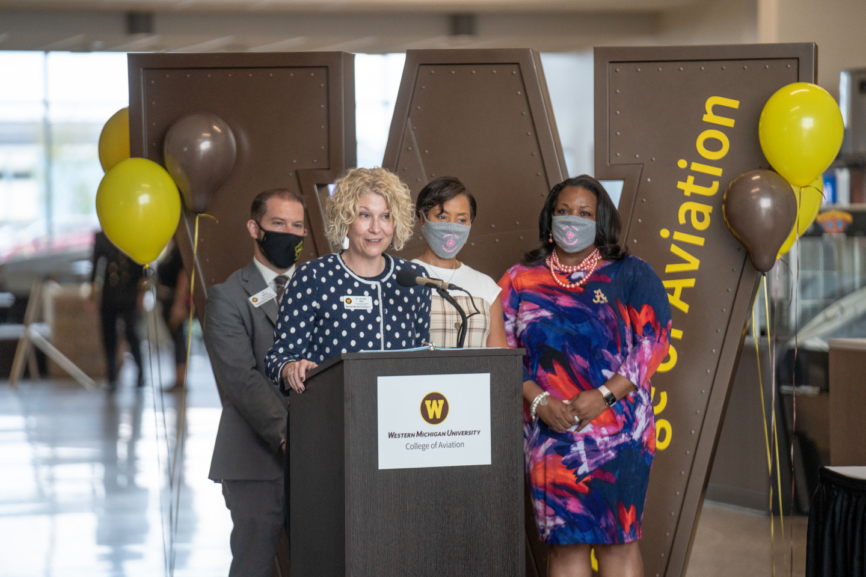 Dr. Jennifer Bott stands at a podium flanked by Dr. Ed Martini, Sonya Bernard-Hollins and Dr. Deveta Gardner.