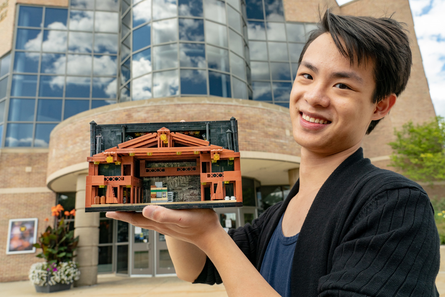 Henry Lee holds one of his Lego minature creations.