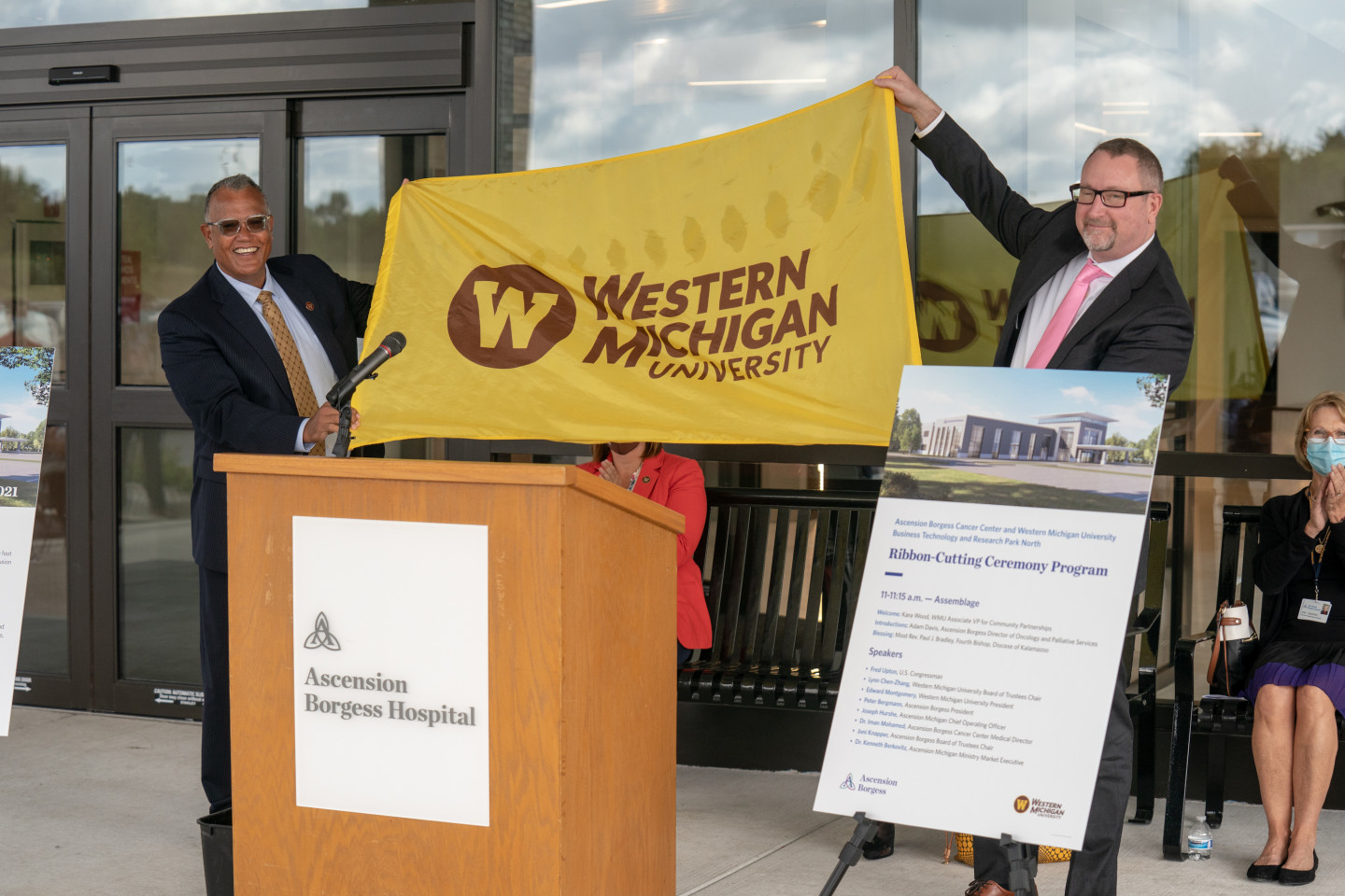 President Montgomery holds up a Western Michigan University flag with President Peter Bergmann of Ascension Borgess in front of the podium of the Ascension Borgess Cancer Center.