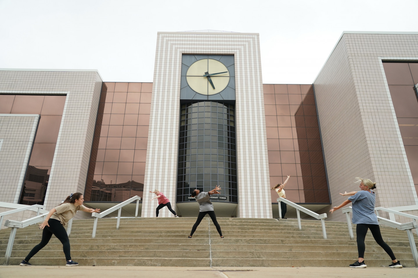Students dance on steps under a clock tower.