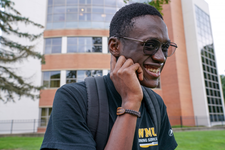 Abondance Kibadi points to his hearing aid.