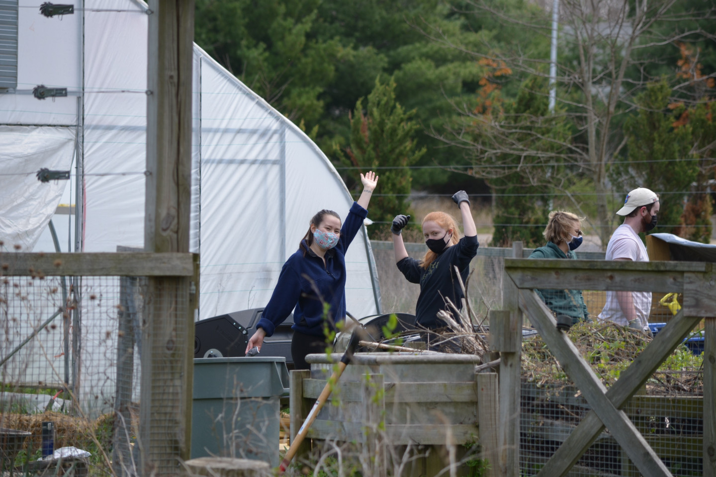 Image shows two students posing in front of the aerated compost pile at Gibbs House