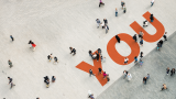 Aerial photo of the word YOU on a street with people walking around on it.