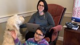 Dr. Laurel Ofstein sitting in chair with son and dog