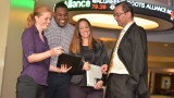 Three students standing with Dr. Arugaslan in front of stock ticker