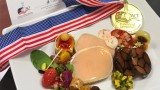 Award-winning food with gold medal placed next to plate