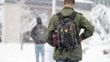 Student walking across campus carrying a backpack in a winter snow storm