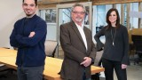 Three professionally dressed people standing in an office
