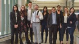 Nine professionally dressed students standing in a hallway