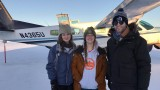 3 students in front of plane in snow