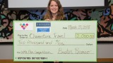 Student standing with oversized check