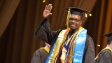 Student in graduation regalia waving