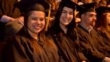 Students wearing caps and gowns at graduation.