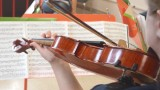 A close up picture of a young woman playing violin from behind her. You can see multiple sheets of music on a music stand.