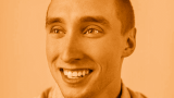 Photo of Drew Everett smiling at camera with an orange filter over the image.