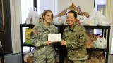 Smiling ROTC cadets presenting WMU's Invisible Need Project with donations and a check