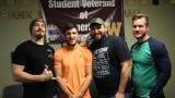 Four student veterans standing in front of a Student Veterans for America banner during the Veterans Day pancake breakfast event.