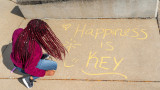 "A student using chalk to write ""Happiness is key"" on campus pavement"