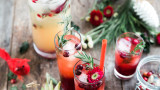 Healthy holiday drinks with holiday decorations around the drinks on a wood table