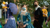 Young woman in beautiful blue, Shakespearian dress, wears matching mask while walking outside.