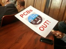 "Shows protest sign reading ""PCBs OUT!."""