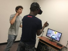 Person using virtual reality equipment in the lab while another person watches.