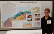 Sarah Vandermeer stands in front of her detailed map of the surficial geology of Pictured Rocks National Lakeshore