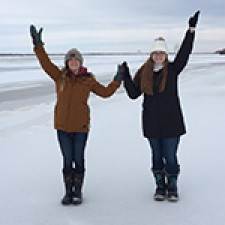 "Two females students standing outide in the snow holding up their arms to make a giant ""W"""