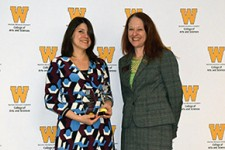 Dr. Alisa Perkins holds awards while standing next to dean Carla Koretsky