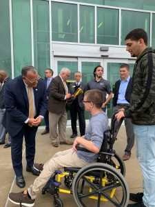 President Edward Montgomery speaks with student Travis Waker, who is seated in his wheelchair.