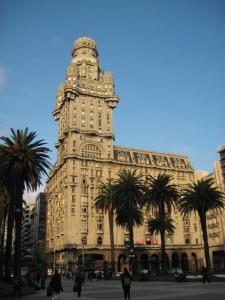 tall building in south america with palm trees in front of it and a blue sky behind