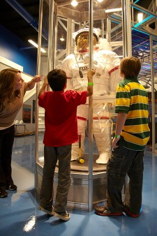 Photo of children looking at a spacesuit exhibit.