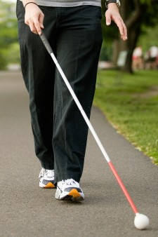Photo of man using a long cane.