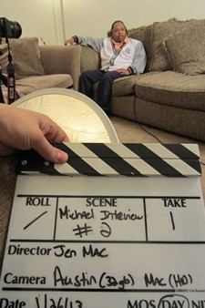 Photo of a clapperboard with Michael Wilder in the background.
