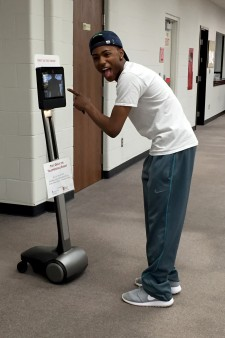 Photo of a student pointing at the robot in Waldo Library.