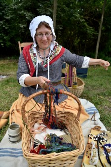 Photo of a woman demonstrating a skill at the Fort St. Joseph archaeological site.