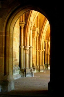 An image of an arched doorway, taken from a dark room, showing a brighter exterior of arched columns.