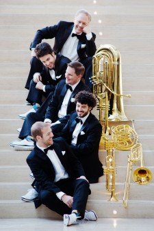 Photo of muscians Canadian Brass holding their instruments and sitting on steps.
