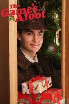 Photo of WMU student Garrett McCord who is dressed up like Sherlock Holmes for hte production of The Game's Afoot, which is also written at the top of the photo. He is stansoing by a Christmas tree in a doorway holding wrapped packages.