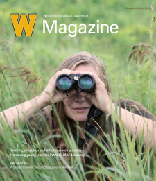 Photo of the cover of WMU Magazine with a woman looking through binoculars sitting in the grass.