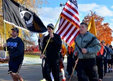 Cadets running through campus holding flags