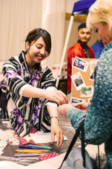 Photo of an international student sharing a cultural skill from her home country with an attendee at one of WMU's annual International Festivals.