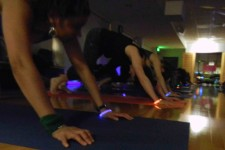 Photo of a row of people wearing various-colored glow sticks while exercising in a darkened room.