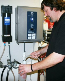 Photo of a WMU custodian filling a spray bottle at an aqueous ozone station.