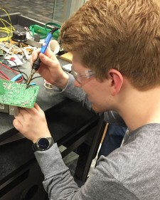 Photo of a student working on a circuit board.